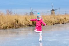 Child ice skating on frozen mill canal in Holland. Child ice skating on frozen canal with wind mills and snow in Holland. Little girl with skates on natural ice stock image