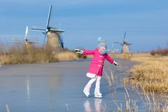 Child ice skating on frozen mill canal in Holland. Child ice skating on frozen canal with wind mills and snow in Holland. Little girl with skates on natural ice royalty free stock image