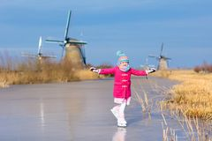 Child ice skating on frozen mill canal in Holland. Child ice skating on frozen canal with wind mills and snow in Holland. Little girl with skates on natural ice stock photos