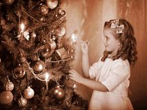 Child ignites candles on Christmas tree. Royalty Free Stock Images