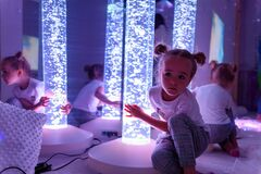 Free Child In Therapy Sensory Stimulating Room, Snoezelen. Autistic Child Interacting With Colored Bubble Tube Lamp During Therapy. Stock Image - 196881521