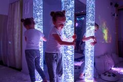 Free Child In Therapy Sensory Stimulating Room, Snoezelen. Autistic Child Interacting With Colored Bubble Tube Lamp During Therapy. Stock Photos - 196881533