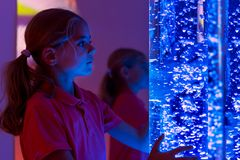 Free Child In Therapy Sensory Stimulating Room, Snoezelen. Child Interacting With Colored Lights Bubble Tube Lamp During Therapy. Royalty Free Stock Photography - 133237187