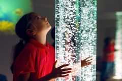 Free Child In Therapy Sensory Stimulating Room, Snoezelen. Child Interacting With Colored Lights Bubble Tube Lamp During Therapy. Stock Image - 139625201