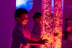 Free Child In Therapy Sensory Stimulating Room, Snoezelen. Child Interacting With Colored Lights Bubble Tube Lamp During Therapy. Royalty Free Stock Images - 139625239