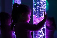 Free Child In Therapy Sensory Stimulating Room, Snoezelen. Child Interacting With Colored Lights Bubble Tube Lamp During Therapy. Stock Photo - 139625240