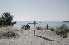 Free Child In White Dress Looking To The Sea And Dancing Stock Image - 181562651