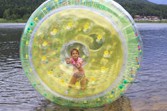 Child in inflatable attraction on lake. Stock Image