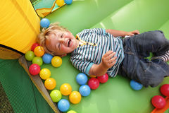 Child on inflatable bouncy castle. 2 year old boy laughing on an inflatable bouncy castle royalty free stock photo
