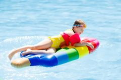 Child on inflatable float in swimming pool. Happy child on inflatable ice cream float in outdoor swimming pool of tropical resort. Summer vacation with kids Royalty Free Stock Photography