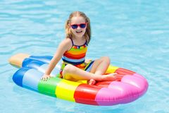 Child on inflatable float in swimming pool. Happy child on inflatable ice cream float in outdoor swimming pool of tropical resort. Summer vacation with kids Stock Photo