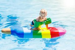 Child on inflatable float in swimming pool. Happy child on inflatable ice cream float in outdoor swimming pool of tropical resort. Summer vacation with kids Royalty Free Stock Images