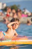 Child on a inflatable mattress, enjoying the sun and sea Stock Photos