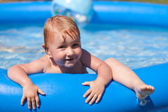 Child in inflatable pool Stock Images