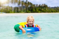 Child on tropical beach. Sea vacation with kids. Child with inflatable ring on beautiful beach. Little boy swimming in exotic sea. Ocean vacation with kid Stock Photography