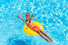 Child  on inflatable ring in swimming pool Stock Photo