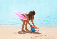 Child with inflatable rubber circle having fun on the beach Royalty Free Stock Photos