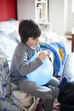 Child with blue balloon. Child with inflated blue balloon for party sitting on sofa Stock Images