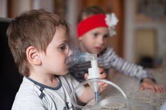 Child, inhalation, healthcare, medicine, asthma, disease , virus, epidemic. Little boy makes inhalation with sitting in front of his sister Royalty Free Stock Images