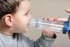Child and inhaler. Close-up image little boy using inhaler for asthma stock images