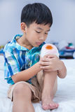 Child injured. Wound on the child's knee with bandage. Stock Image