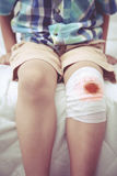 Child injured. Wound on the child's knee with bandage. Vintage s Stock Image