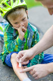 Child with an injury from a fall from a bicycle.  Royalty Free Stock Image