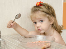 The child with the inquiring views eats porridge Royalty Free Stock Photography