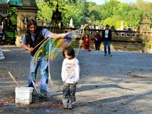 Child inside a water balloon. Entertainer creating a water balloon around a courageous young boy in Central Park, New York City Royalty Free Stock Image