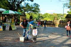Child inside a water balloon. Entertainer creating a water balloon around a courageous young boy in Central Park, New York City Stock Images