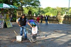 Child inside a water balloon. Entertainer creating a water balloon around a courageous young boy in Central Park, New York City Stock Image