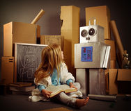 Child Inventor Creating Robot Box. A science student is inventing a metal robot out of cardboard boxes with tools. Use it for an education or imagination concept Stock Photos