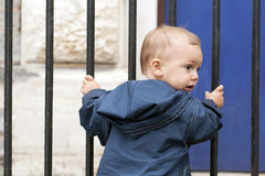 Child at iron gate. A baby or a toddler child holding the bars of iron gate or fence royalty free stock photography
