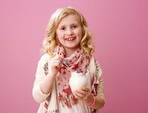 Child isolated on pink background eating farm organic yogurt. Pink mood. Portrait of smiling stylish child with wavy blonde hair isolated on pink background Stock Photography