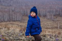 Child in jacket and CAP in the mountains in spring stock photography