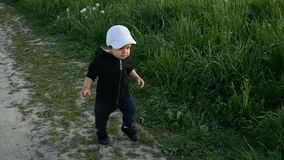 Child in a jacket with a hood and a cap runs in the field along stock footage