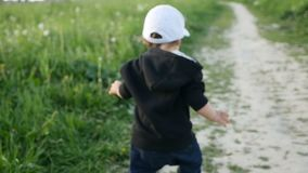 Child in a jacket with a hood and a cap runs in the field along stock video