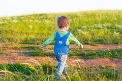 Child in the jeans coverall walk with vigorous strides. Sweet child in the jeans coverall walk with vigorous strides stock photos