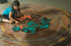 Child with jigsaw puzzle. A little girl sitting on a carpet tries to put together all the pieces of a large jigsaw puzzle Royalty Free Stock Images