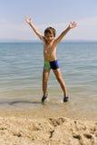 Child jump on seacoast Royalty Free Stock Photos