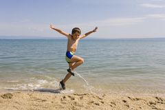 Child jump on seacoast Royalty Free Stock Photography