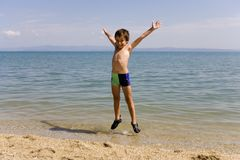 Child jump on seacoast Royalty Free Stock Images