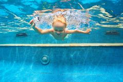 Child jump underwater into swimming pool. Funny portrait of child learn swimming, diving in blue pool with fun - jumping deep down underwater with splashes Royalty Free Stock Photos