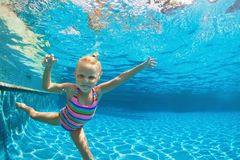 Child jump underwater into swimming pool. Funny portrait of child learn swimming, diving in blue pool with fun - jumping deep down underwater with splashes Stock Images