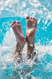 Child jumped water splashes. Child jumped into the pool and his feet can be seen in the spray of water Royalty Free Stock Images
