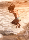 Child jumping on the beach Stock Photos