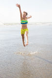 Child jumping at the beach Stock Image