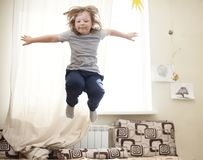 Child jumping on the bed in the bedroom Royalty Free Stock Images