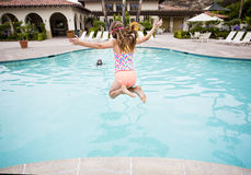 Child jumping into a big swimming pool Royalty Free Stock Photo