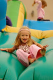 Child on jumping castle. A beautiful blond caucasian girl child with happy expression in the face having lots of fun on a jumping castle on a birthday party in Royalty Free Stock Photo